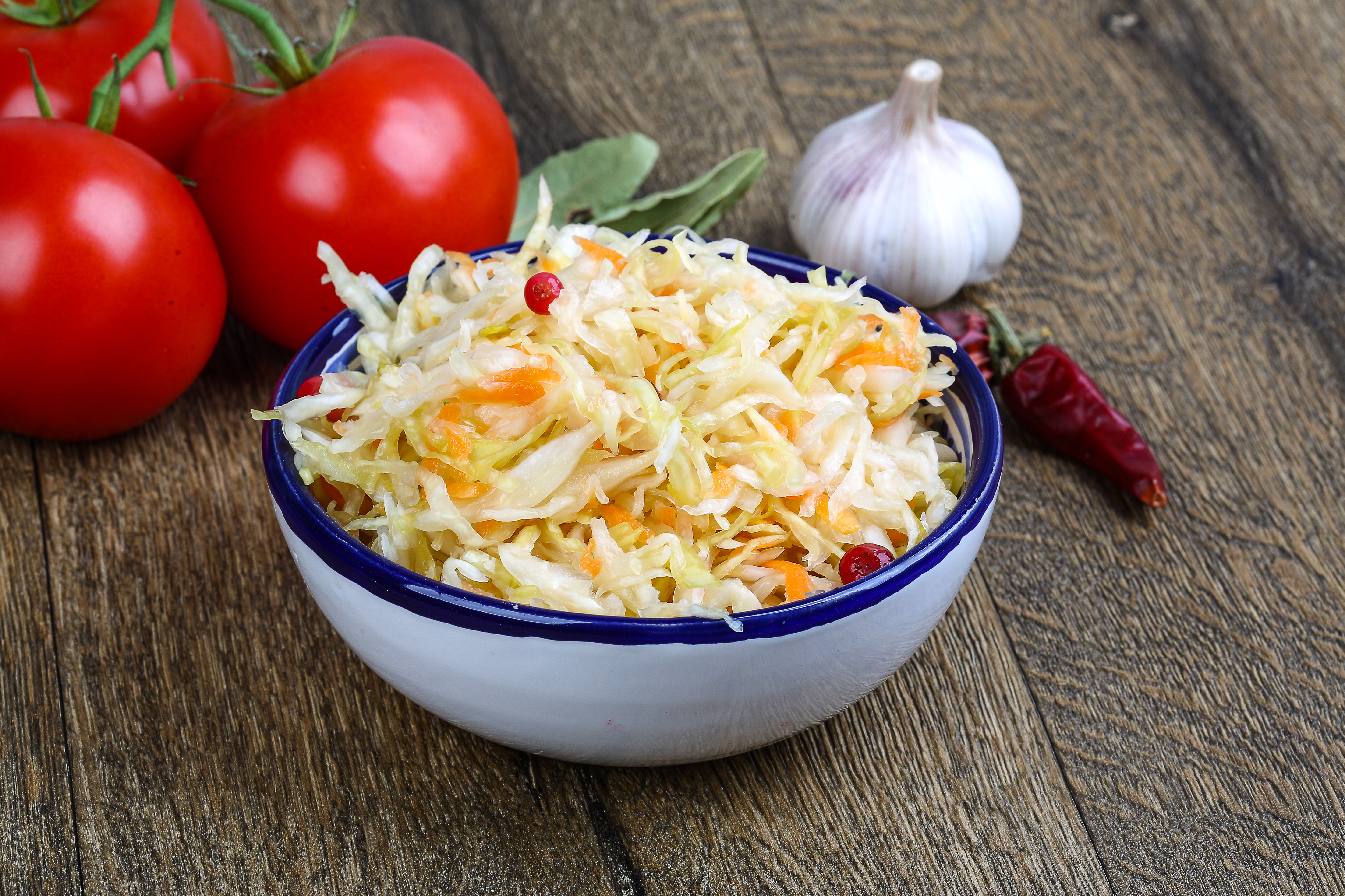 Fermented cabbage - Sauerkraut with herbs and spices on the wood background