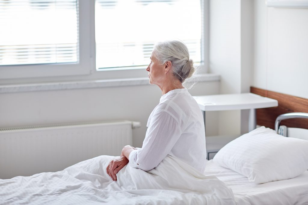 senior woman patient lying in bed at hospital ward