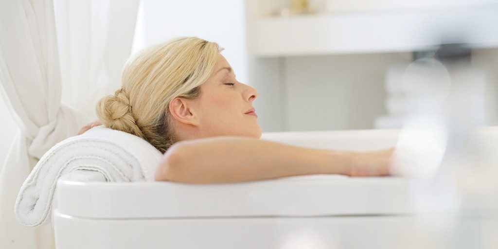 Woman relaxing in epson sal bath to demonstrate healthy salts
